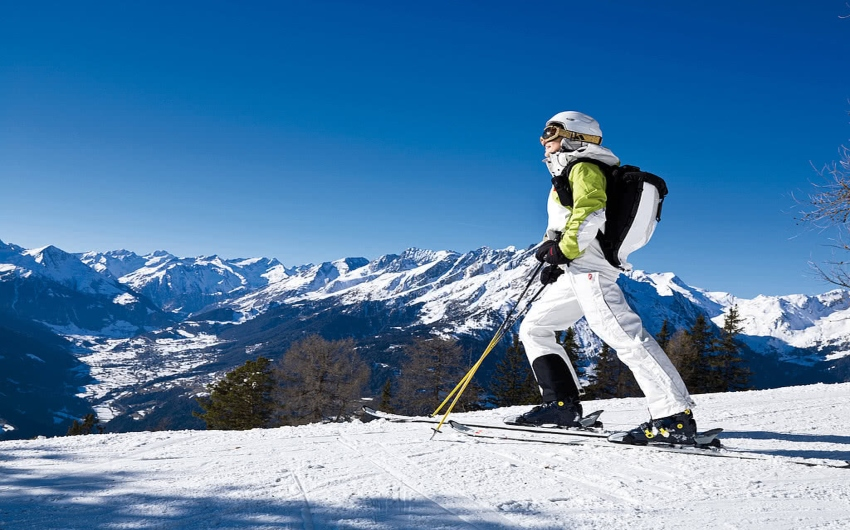 Skier standing on top of a hill